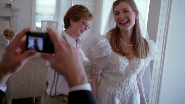 Slow motion medium shot man in suit photographing bride as mother fits her in dress/ Solebury, New York