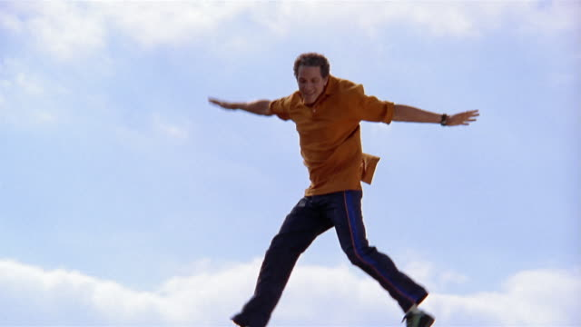 vídeos de stock, filmes e b-roll de slow motion medium shot man jumping up and down on trampoline with sky and clouds in background - camisa pólo