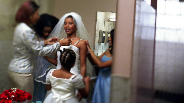 vídeos y material grabado en eventos de stock de slow motion medium shot mirror reflection of black women and girl helping bride get ready in restroom - familia con cuatro hijos