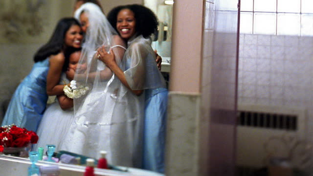 Slow motion medium shot mirror reflection of Black women and girl helping bride hugging