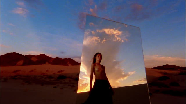 slow motion medium shot mirror with reflection of topless woman walking in desert at sunset / mountain in background - one young woman only stock videos & royalty-free footage
