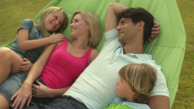 vídeos de stock e filmes b-roll de slow motion medium shot of family in hammock/sotogrande,spain - fotografia de três quartos