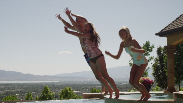 slow motion, medium shot of girls jumping into swimming pool / cedar hills, utah, united states - インフィニティプール点の映像素材/bロール