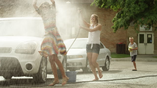 Slow motion medium shot of people having water fight / Pleasant Grove, Utah, United States