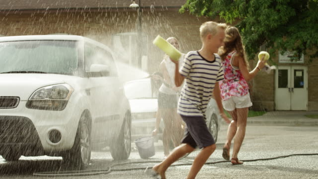 slow motion medium shot of people having water fight / pleasant grove, utah, united states - 水遊び点の映像素材/bロール