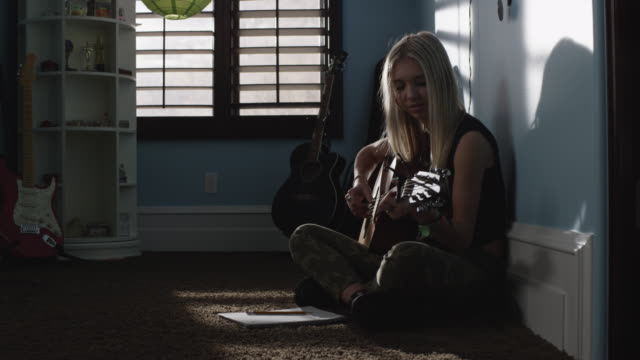 slow motion medium shot of teenage girl writing music and playing guitar / sandy, utah, united states - one teenage girl only stock videos & royalty-free footage