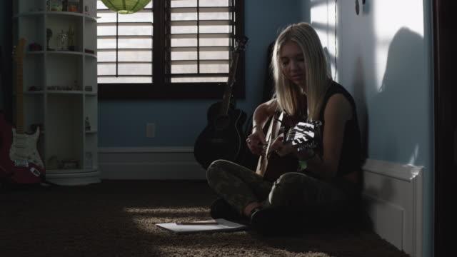 stockvideo's en b-roll-footage met slow motion medium shot of teenage girl writing music and playing guitar / sandy, utah, united states - alleen één tienermeisje