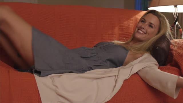 slow motion medium shot of woman lying down on couch/marbella region, spain - 若い女性だけ点の映像素材/bロール