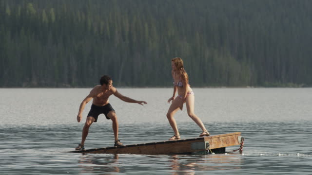 slow motion medium shot of young couple playing on floating dock on lake / redfish lake, idaho, united states - standing water stock videos and b-roll footage