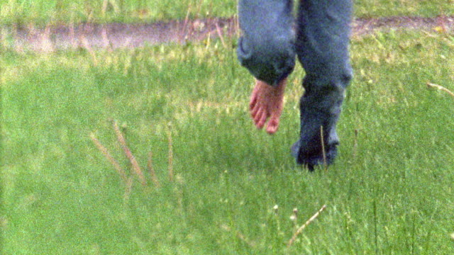 Slow motion medium shot pan barefeet of boy in blue jeans running in grass and jumping in puddle / Missouri