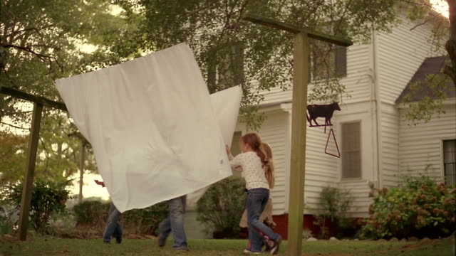 Slow motion medium shot pan four girls running through sheets hanging from clothesline in front of farmhouse