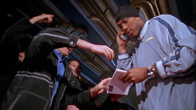 Slow motion medium shot pan hip hop star greeting fans / signing autographs / talking on fan's cell phone