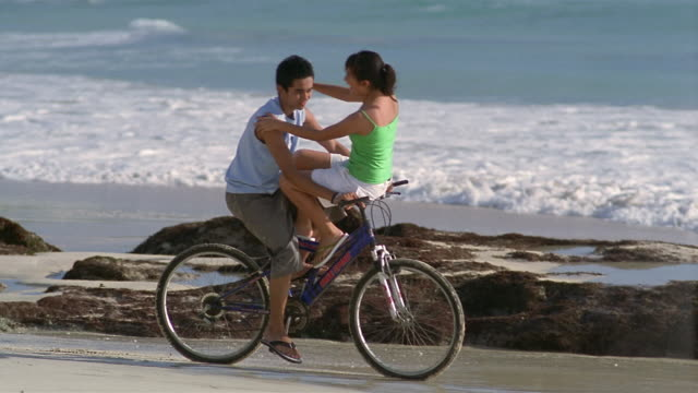 stockvideo's en b-roll-footage met slow motion medium shot pan man riding woman on handlebars of bike along beach/ bali, indonesia - menselijke arm