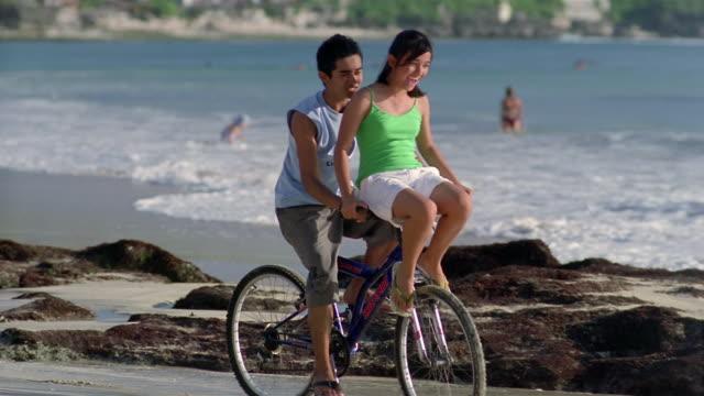 Slow motion medium shot pan man riding woman on handlebars of bike along beach/ Bali, Indonesia