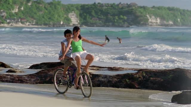 vídeos y material grabado en eventos de stock de slow motion medium shot pan man riding woman on handlebars of bike along beach/ bali, indonesia - manillar