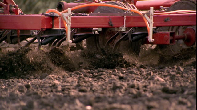 slow motion medium shot pan plow blades dragging through field and turning up soil / clarksville, iowa - plow stock videos and b-roll footage