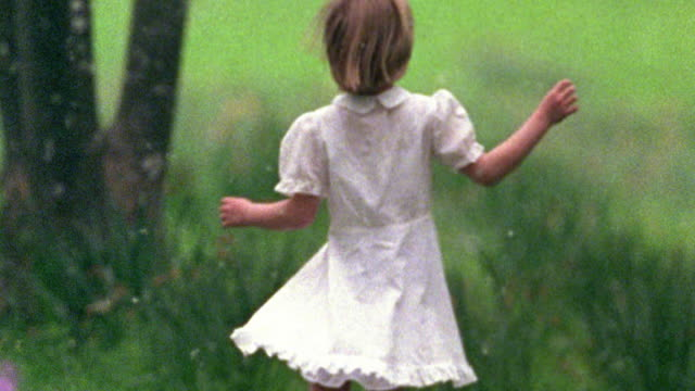 Slow motion medium shot pan rack focus young girl spinning in grass with seeds blowing in wind / Missouri
