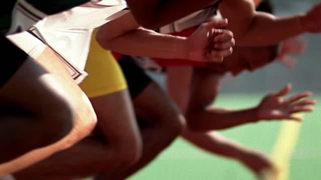 slow motion medium shot pan row of runners starting race - 陸上競技点の映像素材/bロール