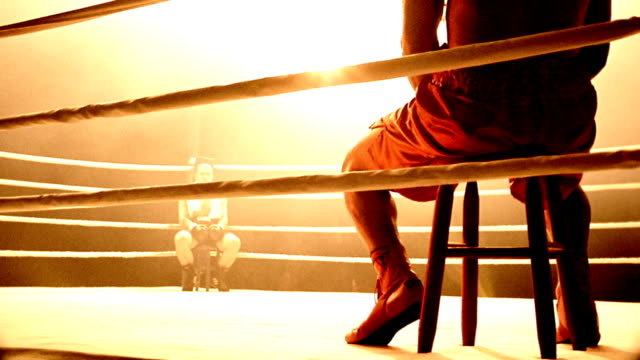 slow motion medium shot pan selective focus boxers sitting in opposite corners of ring facing each other - boxing ring stock videos & royalty-free footage