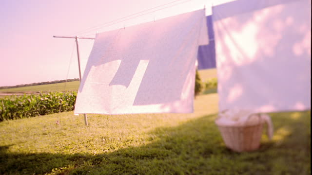 Slow motion medium shot pan sheets hanging on clothesline and blowing in wind with laundry basket on ground / Iowa