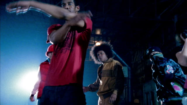 slow motion medium shot people breakdancing in warehouse - baggy jeans stock videos & royalty-free footage