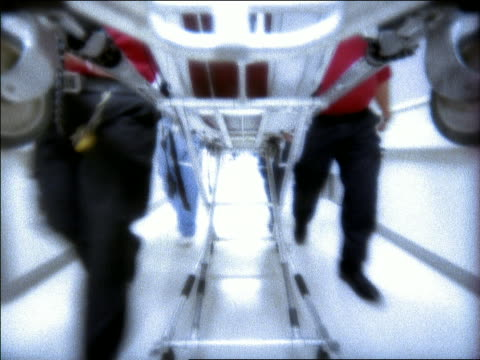 Slow motion medium shot point of view legs of EMTs and hospital personnel pushing gurney down hallway + turning
