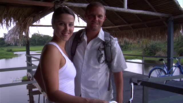 vídeos de stock e filmes b-roll de slow motion medium shot portrait couple with bicycles on deck at ecolodge/ the amazon, brazil - telhado de palha