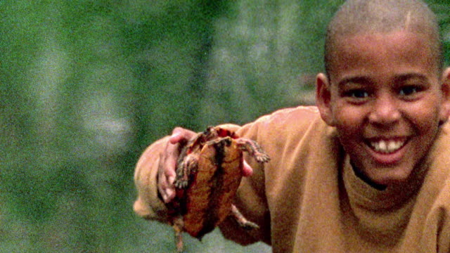 Slow motion medium shot rack focus Black boy holding turtle and smiling at camera with pond in background / Missouri