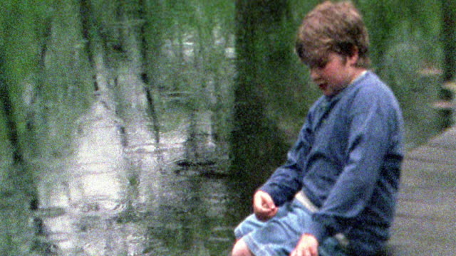 Slow motion medium shot side view boy sitting on dock and throwing rocks in to water with rain falling / Missouri