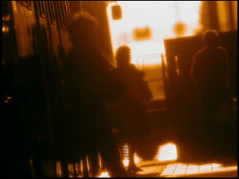vídeos y material grabado en eventos de stock de slow motion medium shot silhouetted commuters exiting train onto platform - imagen virada