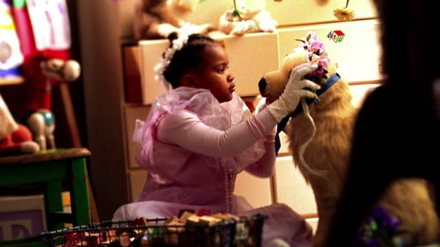 Slow motion medium shot small Black girl in costume playing dress up with stuffed dog