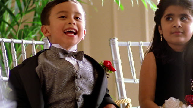 slow motion medium shot small hispanic boy in tuxedo laughing - tuxedo stock videos and b-roll footage