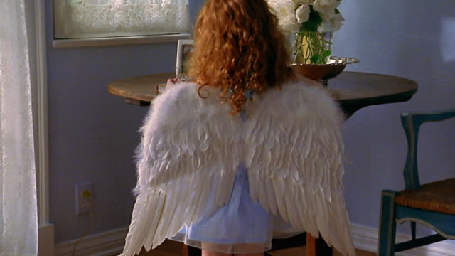 slow motion medium shot small redhead girl wearing angel costume standing at table / zoom out to wide shot - angel点の映像素材/bロール