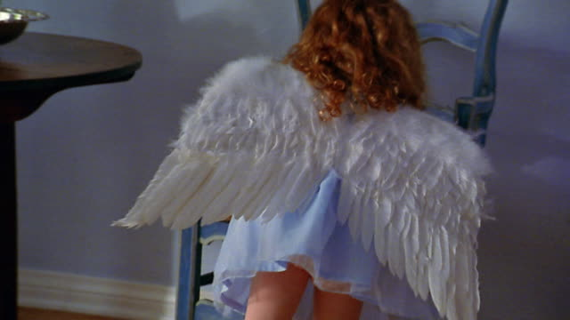 slow motion medium shot small redhead girl wearing angel costume walking up to chair / walking away - angel stock videos & royalty-free footage