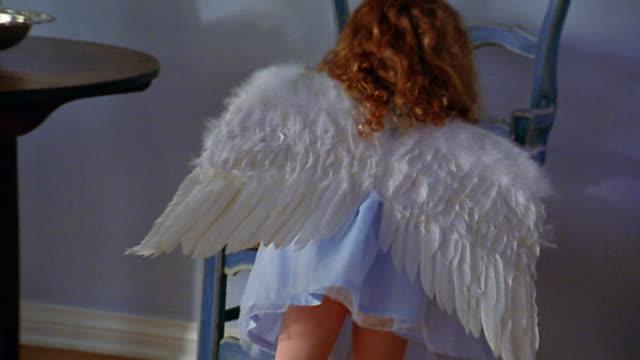 slow motion medium shot small redhead girl wearing angel costume walking up to chair / walking away - ängel bildbanksvideor och videomaterial från bakom kulisserna