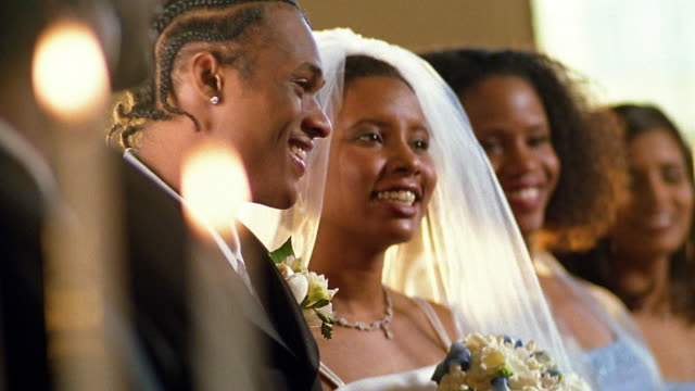 Slow motion medium shot smiling Black couple saying wedding vows / tilt down to clergyman's hands holding Bible