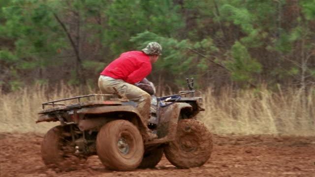 slow motion medium shot teenage boys mudding on 4-wheeled atvs - quadbike stock videos & royalty-free footage