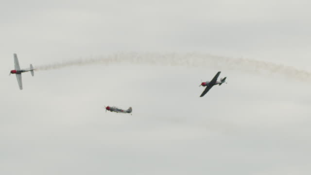Slow motion medium shot three Soviet Yak-52 military propeller aircraft fly in tight formation past camera.