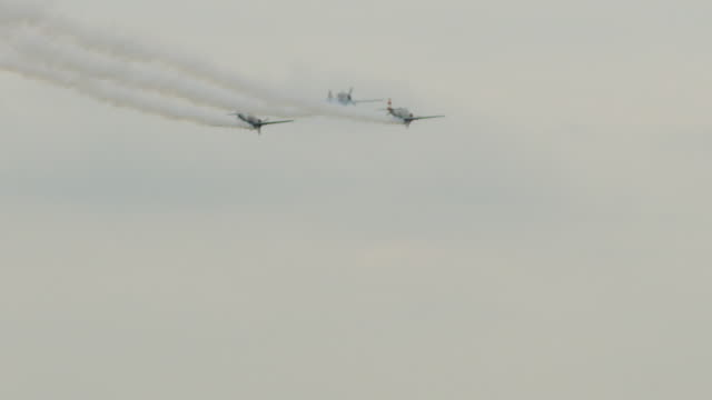 slow motion medium shot three soviet yak-52 military propeller aircraft fly in tight formation; one pulls out into loop-the-loop. - tre oggetti video stock e b–roll
