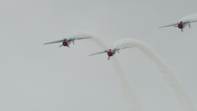 Slow motion medium shot three Soviet Yak-52 military propeller aircraft fly straight down in tight formation past camera.