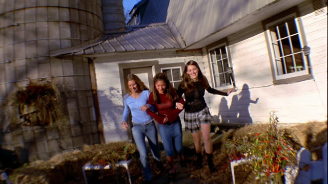 Slow motion medium shot three teen girls running arm-in-arm and laughing outside farmhouse