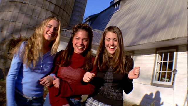 Slow motion medium shot three teen girls standing arm-in-arm and laughing outside house