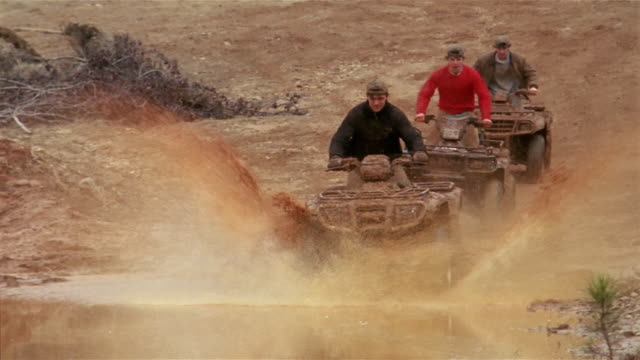 slow motion medium shot three teenage boys riding down hill on 4-wheeled atvs and splashing into large muddy puddle - quadbike stock videos & royalty-free footage