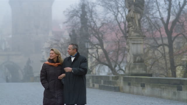 slow motion medium shot tilt down man and woman walking on charles bridge on foggy day / prague - charles bridge stock videos and b-roll footage