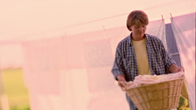 Slow motion medium shot tilt down woman putting laundry basket down on grass with clothesline in background / Shell Rock, Iowa