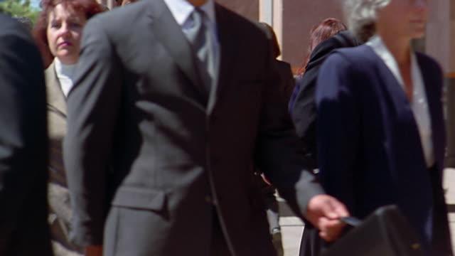 slow motion medium shot tilt up nude man standing on sidewalk / business people walking around him - 30 34 years stock videos and b-roll footage