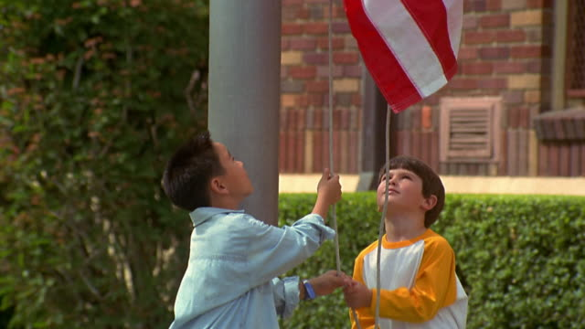 slow motion medium shot tilt up two young boys raise american flag at flagpole in front of school with close up flag rising - hoisting stock videos & royalty-free footage