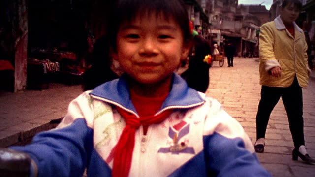 slow motion medium shot tilt up young asian girl in warmup jacket sitting on tricycle on brick street / china - asian market stock videos and b-roll footage