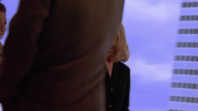 vídeos y material grabado en eventos de stock de slow motion medium shot tracking shot businesswomen entering office and talking with businessman talking on cell phone by window - encuadre de tres cuartos
