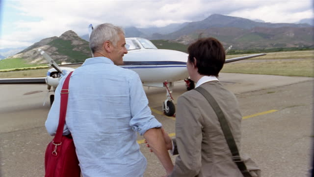 vídeos de stock e filmes b-roll de slow motion medium shot tracking shot couple walking toward private jet and holding hands / corsica - cabelo grisalho